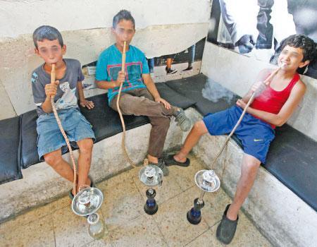 طلبة توجيهي في الأردن يدخنون الارجيلة أمام مدرستهم والفحم داخل المطبخ